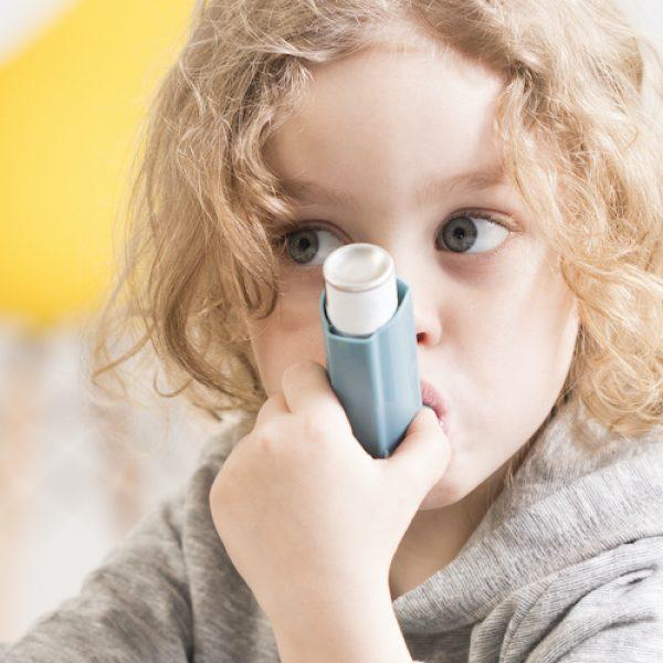 Toddler kid using asthma medicine inhaler for breathing